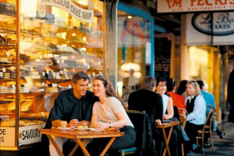 man and woman sitting at a table outside a cake shop