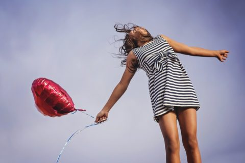 girl in black and white striped dress holding a red balloon looking up at the sky laughing