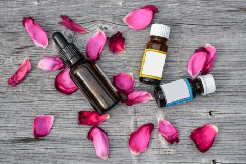 bottles of essential oils and scents laying on piles of rose petals