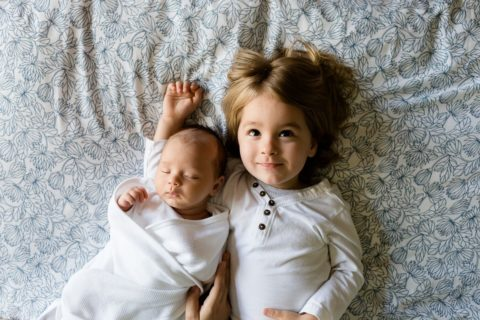 A toddler and his baby brother laying on white sheets with small black swirl designs